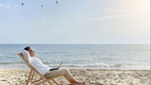 man-with-laptop-computer-relaxing-on-the-beach-300x200-1.jpg